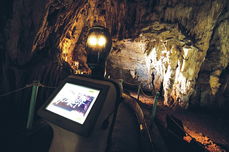 Persephone, the robot guide, leads visitors in a Greek cave